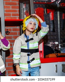 Boy in firefighter uniform in front of the wall of the fire station