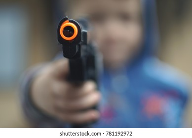 Boy fires with a toy gun pistol. focus on the gun
