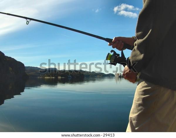 Boy fishing by the ocean