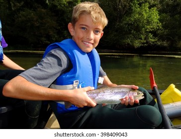 Boy fishing - child fishing from a canoe, proudly holding his catch (Rainbow Trout)