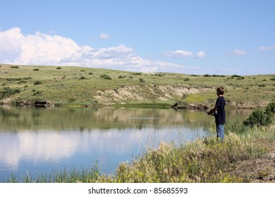 Boy fishing at the edge of a pond on a summer day.