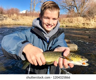 Boy fishing - a handsome child holds a large Brown Trout fish he caught fly fishing