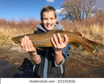 Boy fishing - a handsome child holds a huge Brown Trout fish caught fly fishing
