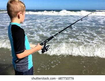 Boy fishing in ocean.