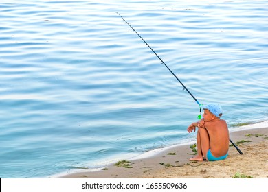 Boy with fishing rod sitting near the lake. Summer vacation time