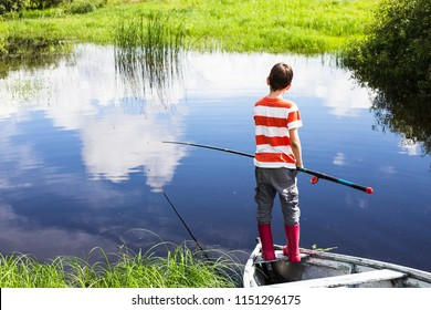 boy with the fishing rod standing on the boat. child fishing alone