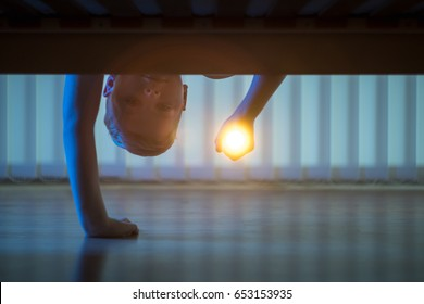 The boy with a flashlight under the bed. night time