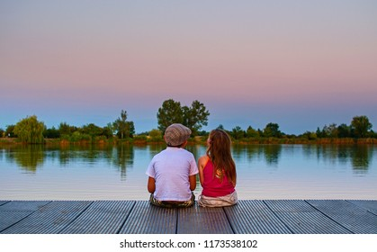 Boy with flat cap and little girl are sitting on pier. Boy and girl are looking upwards on sky. Red and blue sunset on sky. Love, friendship and childhood concept. Beautiful romantic sunset picture.