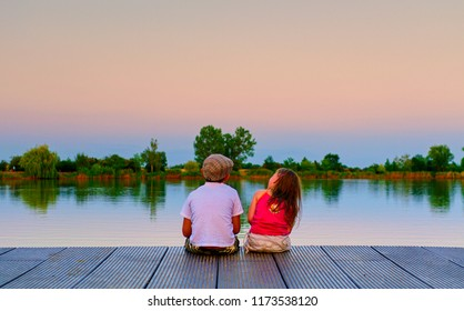 Boy with flat cap and little girl are sitting on pier. Boy and girl are looking upwards on sky. Love, friendship and childhood concept. Beautiful romantic sunset picture.
