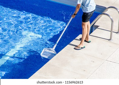 Boy in flip flops cleaning the swimming pool with a net