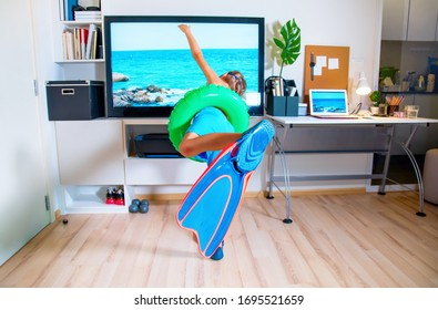 Boy in flippers and swimming ring imitating swimming into the sea near TV. Stay at home. Interior. Isolation. Coronavirus situation at home.