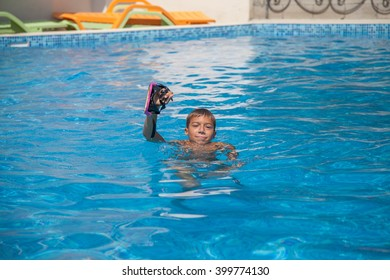 boy floats in the pool with pink mask for diving