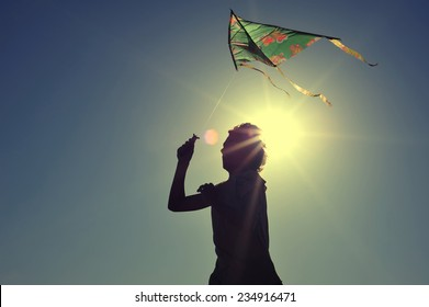 Boy flying a kite on beach at sunrise