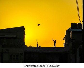 Boy Flying kite on roof in New Delhi, India at Sunset