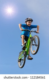 Boy flying on bicycle over sunny blue sky