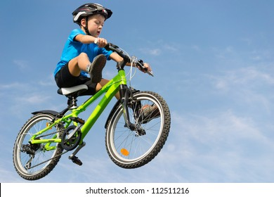 Boy flying on bicycle over blue sky with swept legs
