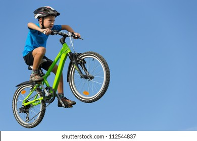 Boy flying on bicycle over clear blue sky