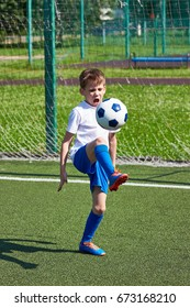 Boy football player training with a ball on the green lawn of the stadium