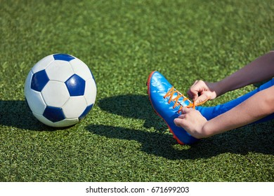 Boy football soccer tying the laces on the boots on a green grass