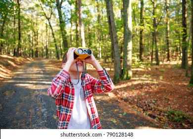 boy in the forest looking up through binoculars. child outdoors with binoculars. The concept of the study of birds