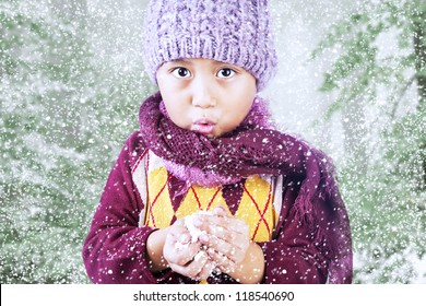 A boy is freezing in  cold winter weather wearing winter hat and scarf