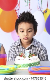 Boy with in front of  birthday cake with sad expression