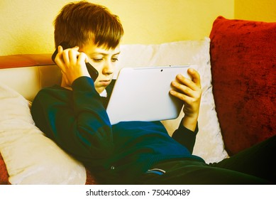 Boy frustrated watching a video on a tablet pc and talking on a cell phone habits of children, modern technology