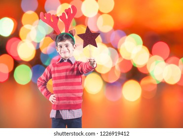 Boy full of Christmas spirit with elf hat holding a red star with copy space