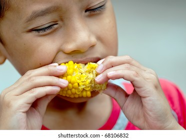 a boy was fun while eating boiled corn