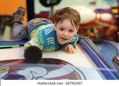 Boy gamble in air hockey at tha amusement park