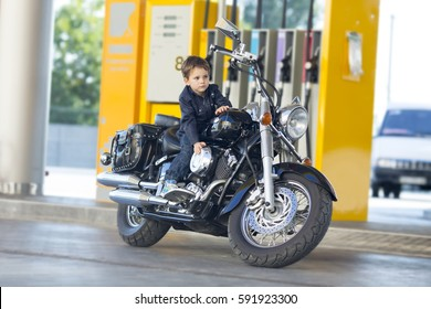 boy at the gas station waiting for his girlfriend sitting on a motorcycle