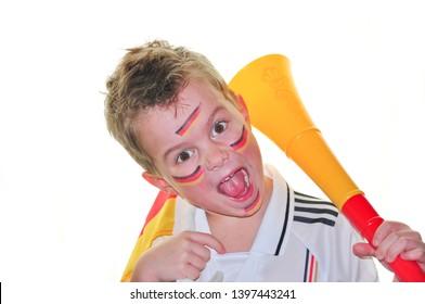 A boy with Germany jersey and vuvuzela on white background