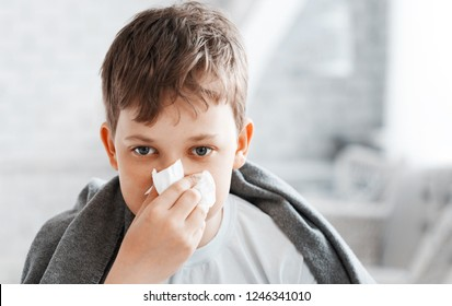 Boy get cold and blow her nose at home.