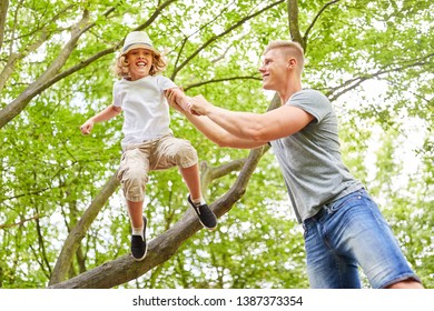 Boy gets help from his father when jumping from the tree