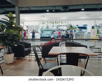 Boy Getting Bored Sitting on a Chair at Restaurant