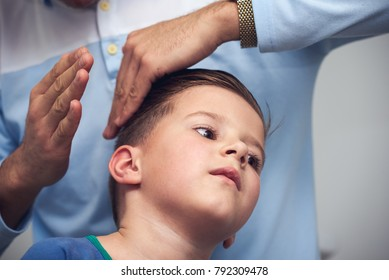 Boy getting a hairstyling in barbershop.