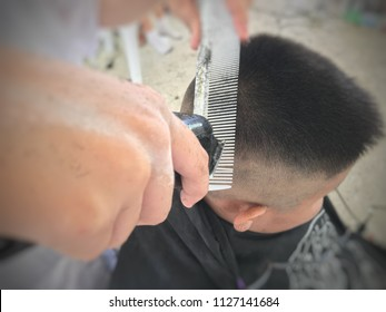 boy getting his head shaved by barber, An Asian teen head with short hair cut, Male child at the barber shop to cut the hair, selective focus.