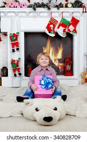 boy with a gift by the fireplace on Christmas Eve