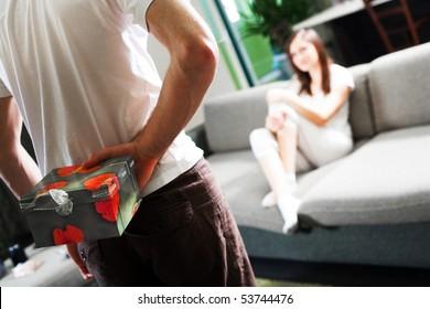Boy with gift and girl on sofa