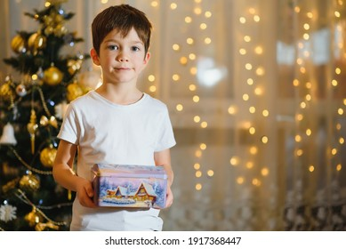 boy with a gift near the Christmas tree