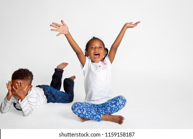 Boy and girl African American siblings.  The girl is center, arms in the air, mouth wide open, a total extrovert.  The boy is laying on his stomach with his hands covering his face like an introvert.