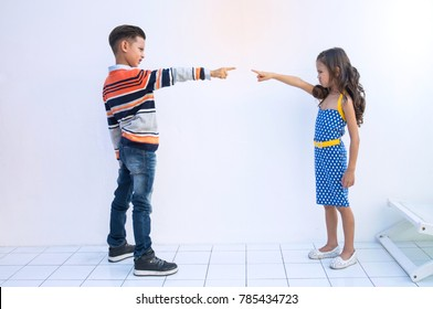 Boy and girl angrily pointing fingers at each other.