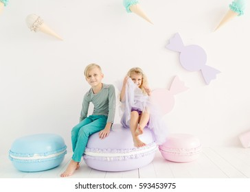 Boy and girl in a bright colored clothing in the children's room with large macaroon. Brother and sister having fun