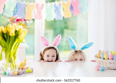 Boy and girl in bunny ears at breakfast on Easter morning at table with Easter eggs basket. Kids celebrating Easter. Children on Easter egg hunt. Home decoration - pastel bunny banner and flowers