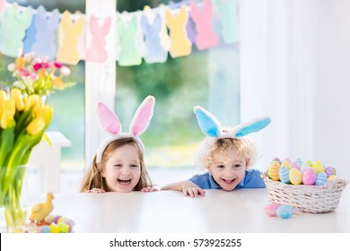 Boy and girl in bunny ears at breakfast on Easter morning at table with Easter eggs basket. Kids celebrating Easter. Children on Easter egg hunt. Home decoration, pastel bunny banner and flowers