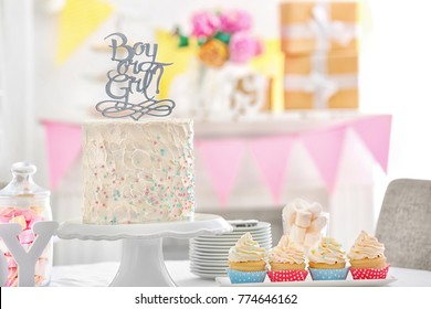 """""""Boy or girl"""" cake and cupcakes for baby shower party on table indoors"""