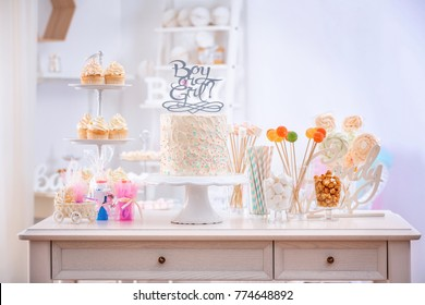 """""""Boy or girl"""" cake and different treats for baby shower party on table indoors"""