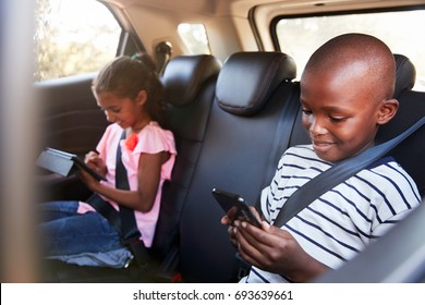 Boy and girl in a car using tablet and smartphone on a trip