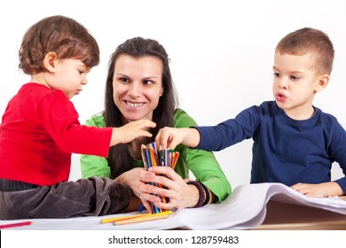 Boy and girl choosing crayons which mom is holding in hands