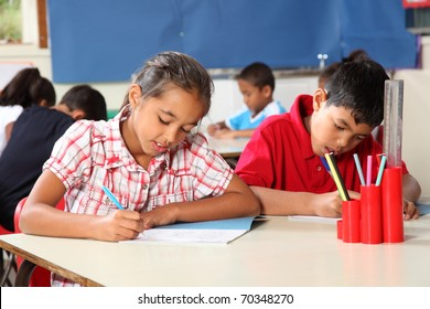 Boy and girl in classroom concentrating on lesson